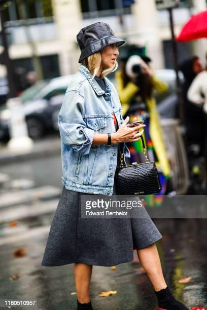 Guest wears a shiny black vinyl rain hat, a light blue washed-out denim jacket with a studded collar, a grey skirt, a shiny black crocodile pattern...