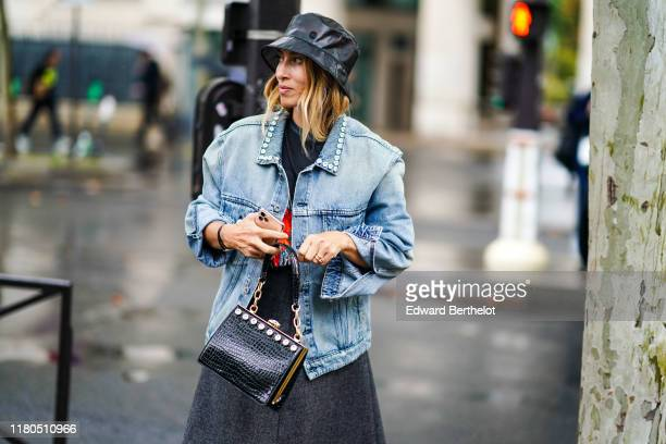 Guest wears a shiny black vinyl rain hat, a light blue washed-out denim jacket with a bejeweled collar, a grey skirt, a shiny black crocodile pattern...