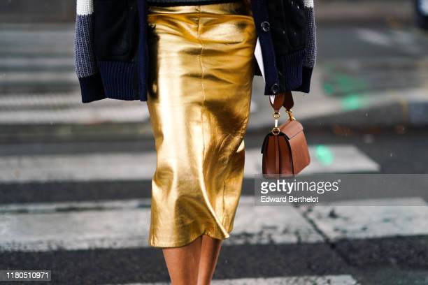 Guest wears a shiny gold color leather skirt, a tan-color bag, outside Miu Miu, during Paris Fashion Week - Womenswear Spring Summer 2020, on October...