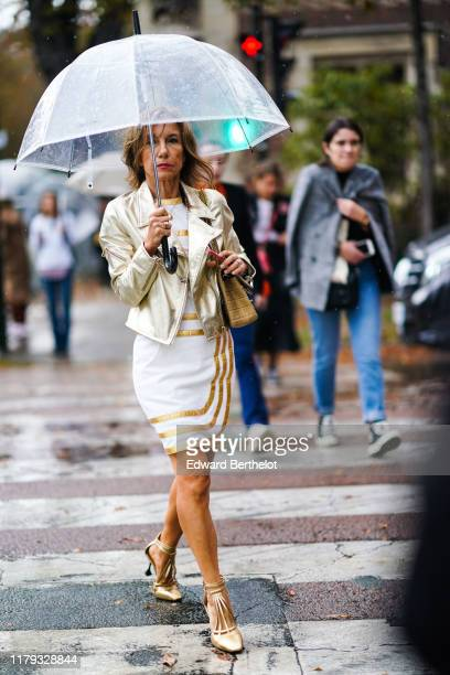 Guest wears a shiny golden leather jacket, a white dress with golden inserts, golden high heels shoes, holds a clear plastic umbrella, under the...