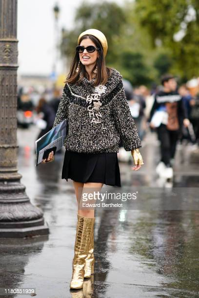 Guest wears a shiny gold-tone leather Chanel hat, sunglasses, Chanel earrings, a heather black and gold-tone cowl-collar sweater, Chanel brooches,...