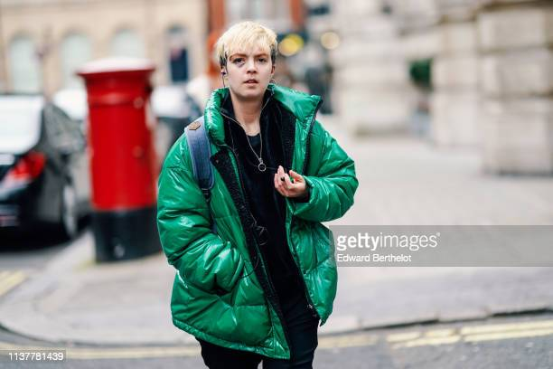A guest wears a shiny green puffer jacket a black front zip sweater during London Fashion Week February 2019 on February 16 2019 in London England