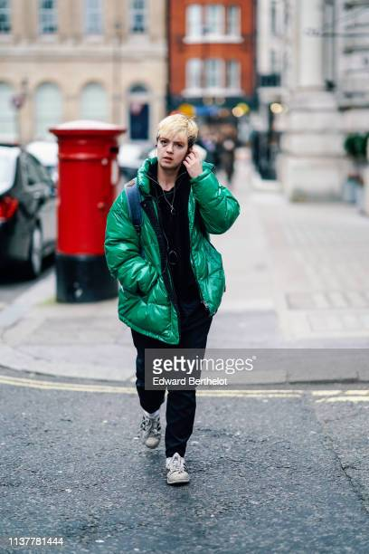 A guest wears a shiny green puffer jacket a black front zip sweater black pants white sneakers during London Fashion Week February 2019 on February...