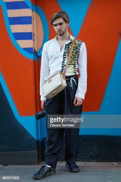 A guest wears a shirt a Gucci bag pants holds a camera during London Fashion Week Men's January 2018 at on January 7 2018 in London England