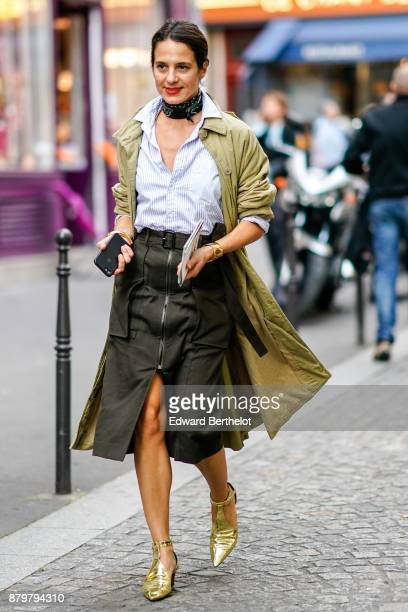 A guest wears a shirt a skirt gold shoes a trench coat a scarf choker outside Koche during Paris Fashion Week Womenswear Spring/Summer 2018 on...