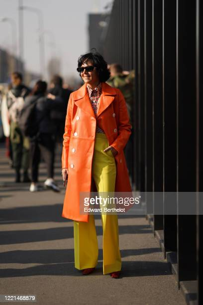 Guest wears a shirt, an orange leather trench coat, yellow pants, outside Gucci, during Milan Fashion Week Fall/Winter 2020-2021, on February 19,...