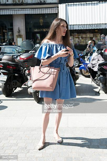 Guest wears a shoulderless dress Valentino shoes and Gucci bag on day 2 of Paris Collections Men on June 23 2016 in Paris France Guest
