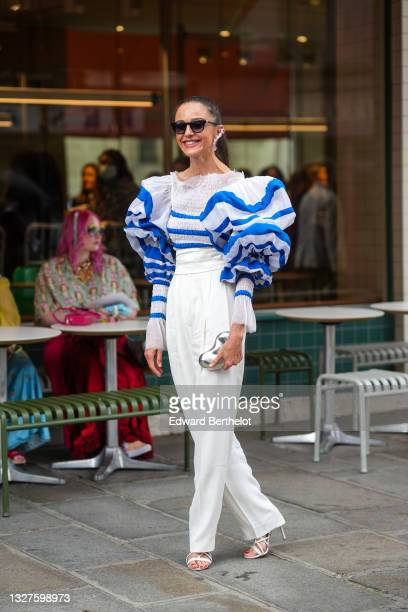 Guest wears a silver and crystals pendant large earring, black sunglasses, a white with blue striped ruffled large puffy long sleeves t-shirt, white...