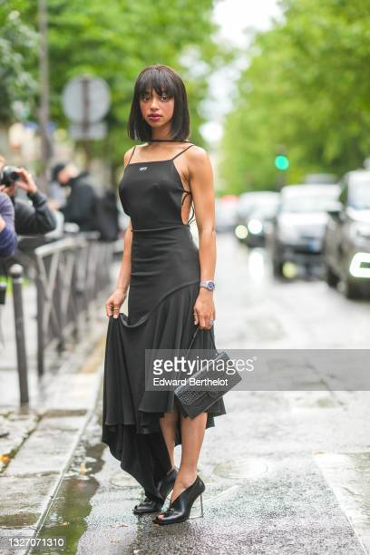 Guest wears a silver chain necklace, a black strappy long asymmetric flowing dress from Off-White, a silver watch, a black shiny leather crocodile...
