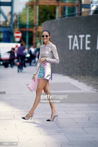 A guest wears a silver glitter top a shiny skirt a pink clutch heels shoes during London Fashion Week September 2018 on September 17 2018 in London...