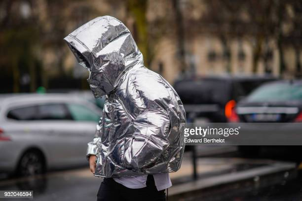 A guest wears a silver hooded puffer during Paris Fashion Week Womenswear Fall/Winter 2018/2019 on March 4 2018 in Paris France