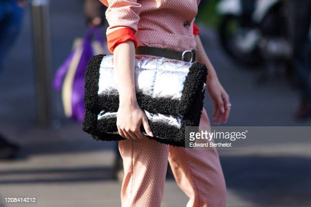 Guest wears a silver quilted shiny bag with black fluffy parts, outside BOSS, during Milan Fashion Week Fall/Winter 2020-2021 on February 23, 2020 in...