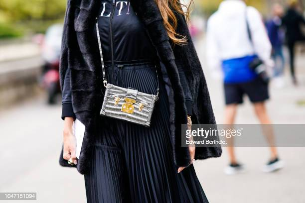 A guest wears a silver rigid Vuitton case bag outside Valentino during Paris Fashion Week Womenswear Spring/Summer 2019 on September 30 2018 in Paris...