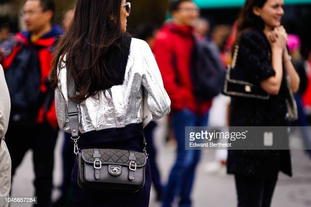 A guest wears a silver shiny glitter jacket a Chanel bag outside Chanel during Paris Fashion Week Womenswear Spring/Summer 2019 on October 2 2018 in...