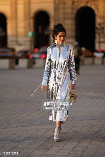 A guest wears a silver shiny glitter turtleneck dress an Ashaped earring a yellow and purple bejeweled bag striped socks bejeweled shoes outside...