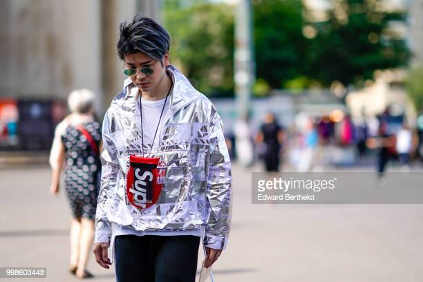 A guest wears a silver shiny jacket a Supreme bag outside OffWhite during Paris Fashion Week Menswear SpringSummer 2019 on June 20 2018 in Paris...