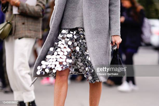 A guest wears a silver shiny sequin skirt outside Chanel during Paris Fashion Week Womenswear Spring/Summer 2019 on October 2 2018 in Paris France