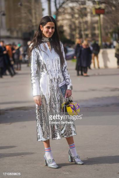 Guest wears a silver shiny sequined glittering dress, a yellow and purple bejeweled bag, socks, shoes, outside Chanel, during Paris Fashion Week -...