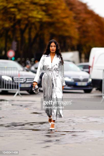 A guest wears a silver shiny trench coat a bag outside Chanel during Paris Fashion Week Womenswear Spring/Summer 2019 on October 2 2018 in Paris...