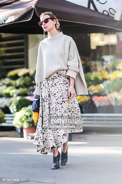 Guest wears a skirt with printed flowers, a white top, a yellow clutch, and sunglasses, outside of the Hermes show during Paris Fashion Week Spring...