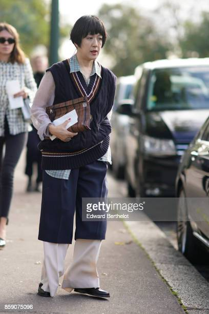 A guest wears a sleeveless wool pull over large bi color pants outside CDG Comme des Garcons during Paris Fashion Week Womenswear Spring/Summer 2018...