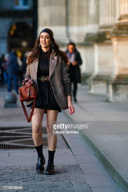 Guest wears a small hat, a brown Chloe bag, a jacket, a short dress, a belt, black socks, black leather shoes, long earrings, outside Vuitton, during...