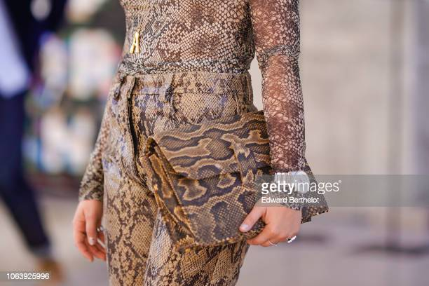 A guest wears a snake print dress a watch and a snake print bag during Paris Fashion Week Womenswear Spring/Summer 2019 on September 26 2018 in Paris...