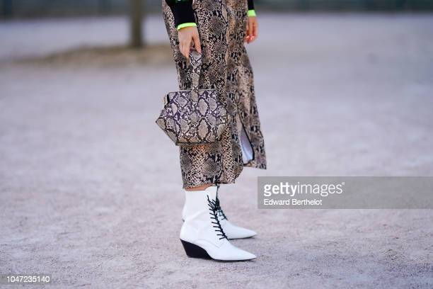 A guest wears a snake print dress and a snake print bag white shoes outside Elie Saab during Paris Fashion Week Womenswear Spring/Summer 2019 on...