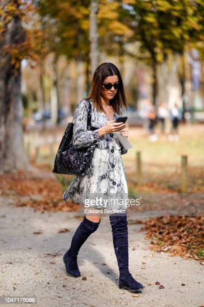 A guest wears a snake print dress outside Akris during Paris Fashion Week Womenswear Spring/Summer 2019 on September 30 2018 in Paris France