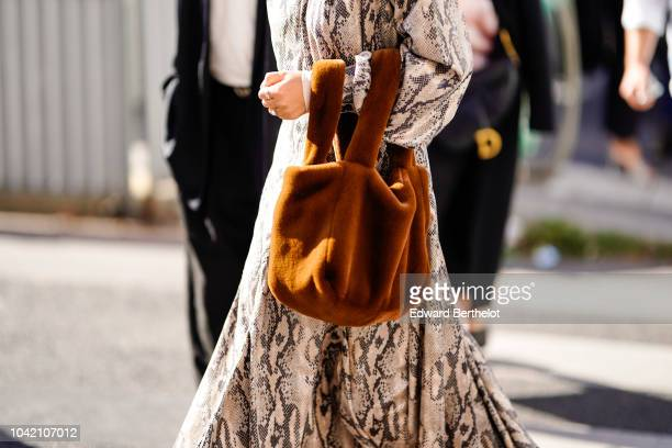 A guest wears a snake print white dress a brown fluffy bag outside Chloe during Paris Fashion Week Womenswear Spring/Summer 2019 on September 27 2018...