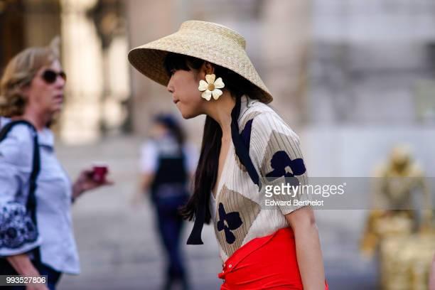 A guest wears a straw hat flower earrings outside Schiaparelli during Paris Fashion Week Haute Couture Fall Winter 2018/2019 on July 2 2018 in Paris...