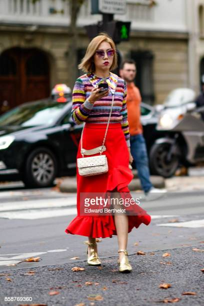 A guest wears a striped colored top a red ruffle skirt a bag golden shoes outside Valentino during Paris Fashion Week Womenswear Spring/Summer 2018...