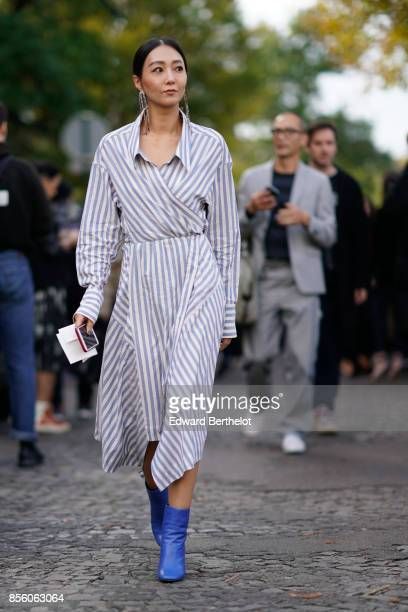 A guest wears a striped dress blue shoes outside CDG Comme des Garcons during Paris Fashion Week Womenswear Spring/Summer 2018 on September 30 2017...