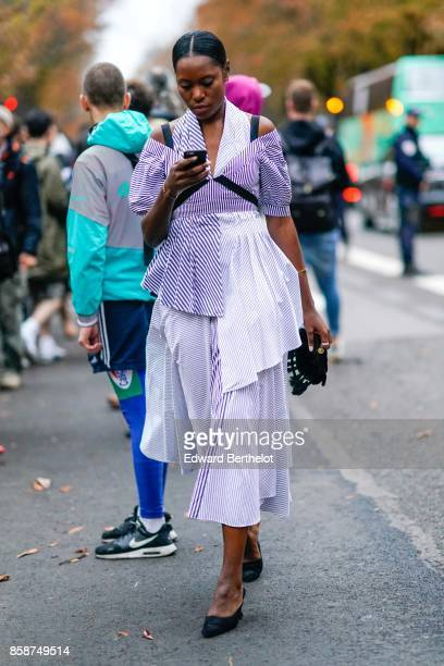 A guest wears a striped dress outside John Galliano during Paris Fashion Week Womenswear Spring/Summer 2018 on October 1 2017 in Paris France