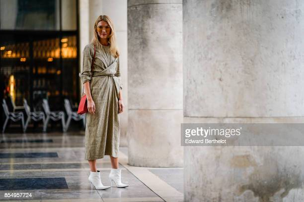 A guest wears a striped dress outside the Lemaire show during Paris Fashion Week Womenswear Spring/Summer 2018 on September 27 2017 in Paris France