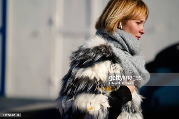 A guest wears a striped fluffy faux fur winter coat a brown Chanel bag gray pants black shoes a gray scarf white Apple airpods outside Dior during...