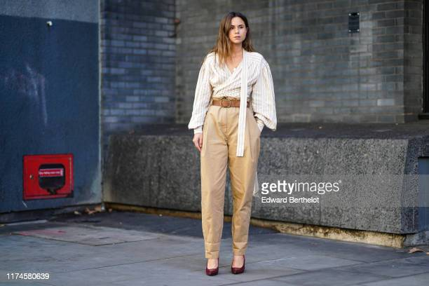 A guest wears a striped shirt a brown leather belt beige pants shoes during London Fashion Week September 2019 on September 13 2019 in London England