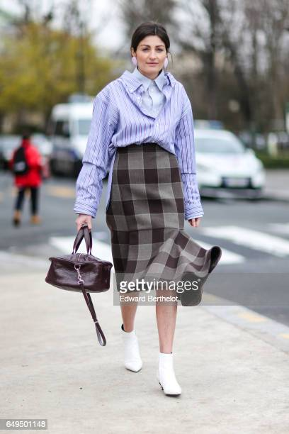 A guest wears a striped shirt a leather bag a checked skirt and white shoes outside the Chanel show during Paris Fashion Week Womenswear Fall/Winter...