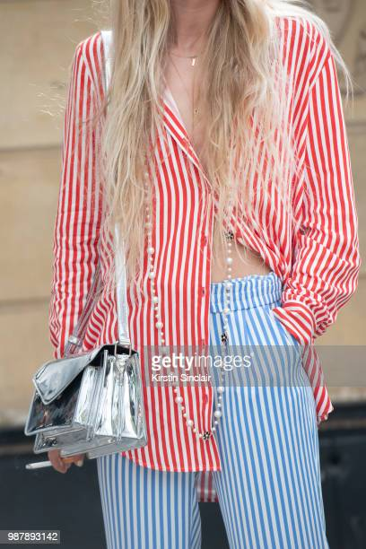 A guest wears a striped shirt and trousers with a silver bag during London Fashion Week Men's on June 10 2018 in London England
