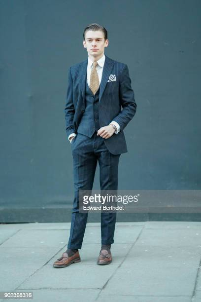 A guest wears a striped suit and a tie during London Fashion Week Men's January 2018 at on January 7 2018 in London England