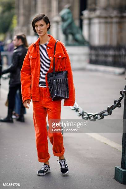 A guest wears a striped top an orange corduroy pantsuit a black bag black sneakers outside the Dries Van Noten show during Paris Fashion Week...