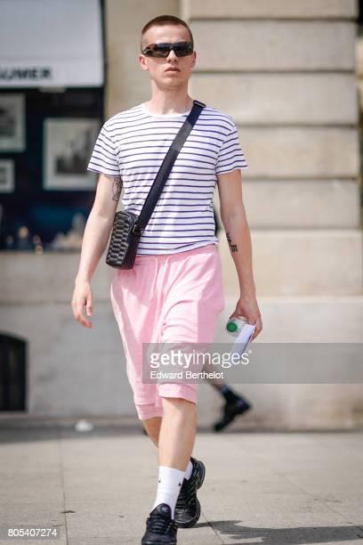 A guest wears a striped tshirt sunglasses a black bag pink cropped pants white socks black shoes outside the Sean Suen show during Paris Fashion Week...
