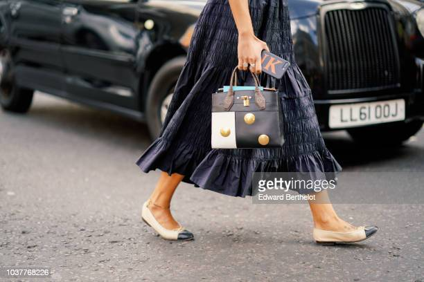 A guest wears a studded black and white bag Chanel slingback shoes during London Fashion Week September 2018 on September 15 2018 in London England