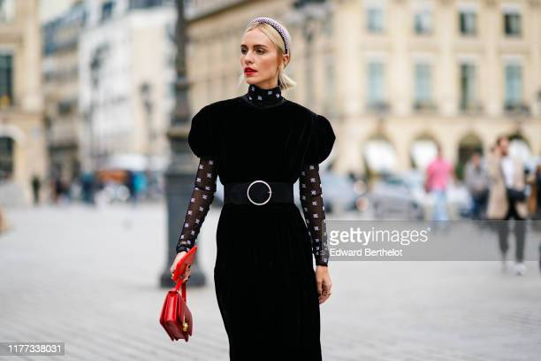 A guest wears a studded headband a black velvet dress with puff sleeves a transparent black hineck top with white pattern print a large black belt...