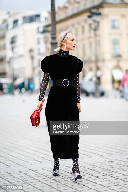 Guest wears a studded headband, a black velvet dress with puff sleeves, a transparent black hi-neck top with white pattern print, a large black belt...