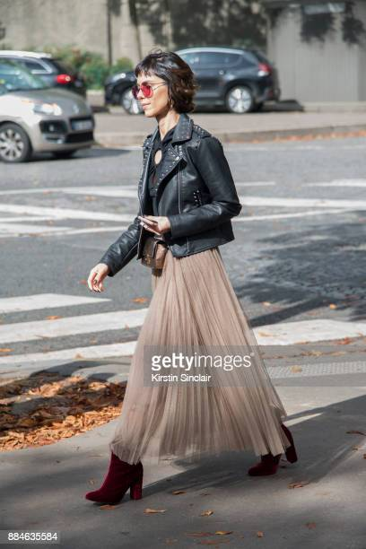 A guest wears a studded leather jacket red velvet shoes sheer tulle pleated skirt and red sunglasses day 5 of Paris Womens Fashion Week Spring/Summer...