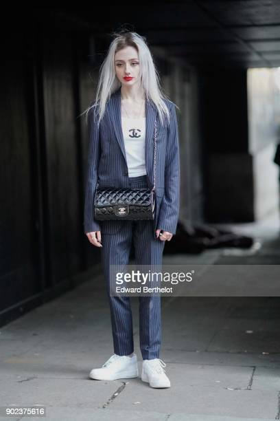 A guest wears a suit a white chanel tshirt a chanel bag white sneakers during London Fashion Week Men's January 2018 at on January 7 2018 in London...