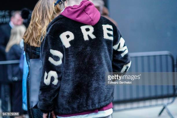 A guest wears a Supreme black fluffy jacket with a purple hood during London Fashion Week Men's January 2018 at on January 6 2018 in London England