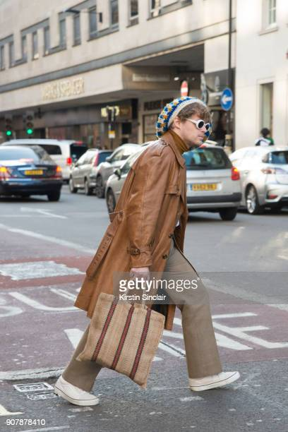 A guest wears a tan leather coat and knitted hat with white sunglasses day 2 of London Mens Fashion Week Autumn/Winter 2018 on January 07 2018 in...