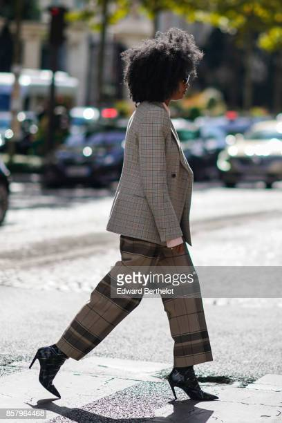 A guest wears a tartan blazer jacket cropped checkered pants black shoes has an afro haircut outside Miu Miu during Paris Fashion Week Womenswear...